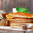 Stack of pancakes with honey and butter on rustic wooden background — Stock Photo #62123239