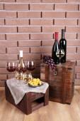 Botellas y vasos de vino, queso y uvas maduras en mesa en ladrillo de la pared fondo — Foto de Stock