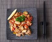 Chinese noodles with vegetables and seafood on plate on bamboo mat background — Stock Photo