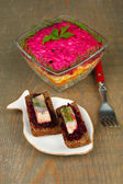 Russian herring salad in glass bowl and sandwiches with salted herring, on wooden table background — Stok fotoğraf