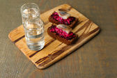Canape herring with beets on rye toasts, on wooden board, and glass of vodka on wooden table background — Photo
