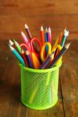 Colorful pencils with scissors in metal holder on rustic wooden background — Photo