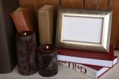 Photo frame with candles and books on wooden surface and wooden wall background — ストック写真