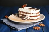 Tasty tiramisu cake on plate, on wooden table, on black background — Stock Photo