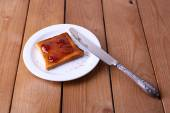 Toast bread spread with jam on plate with knife on wooden table background — Stock fotografie