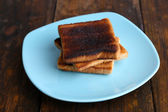 Burnt toast bread on turquoise plate, on wooden table background — Stock Photo