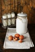 Milk can with eggs, eggshell and  glass bottles on rustic wooden background — Stock Photo