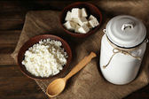 Milk can with cottage cheese on wooden background — Stock Photo