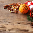 Orange with present box, spices, slices of dried lemon and sprigs of Christmas tree on rustic wooden background — Stock Photo #62216351