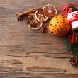 Orange with present box, spices, slices of dried lemon and sprigs of Christmas tree on rustic wooden background — Stock Photo #62216359