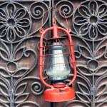 Kerosene lamp on wrought iron gates background — Stock Photo #62217563
