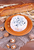 Blue cheese on earthenware dish with nuts, baguette and hay on burlap cloth and wooden table background — Stock Photo