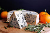 Blue cheese with sprigs of rosemary and oranges on wooden board and dark background — Stock Photo