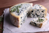 Blue cheese with sprigs of rosemary on sheets of paper and wooden table background — Stock Photo