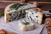 Blue cheese with sprigs of rosemary and nuts on board with sheet of paper and wooden table background — Stock Photo