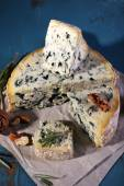 Blue cheese with sprigs of rosemary and nuts on sheet of paper and color wooden table background — Stock Photo
