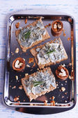 Crispbread with blue cheese and sprigs of rosemary on metal tray and color wooden table background — Stock Photo