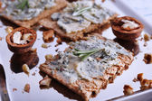Crispbread with blue cheese, nuts and sprigs of rosemary on metal tray and color wooden table background — Stock Photo