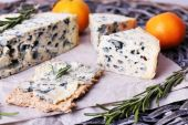 Blue cheese with sprigs of rosemary and oranges on wicker mat background — Stock Photo