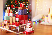 Present boxes on sledge on wooden floor near Christmas tree, indoors — Stock Photo