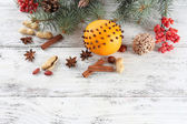 Orange with spices, rowan, and Christmas pine sprig on color wooden background — Stock Photo