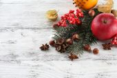 Fruits with spices, rowan, and Christmas pine sprig on color wooden background — Stock Photo