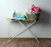Ironing board with laundry on light background — Stock Photo