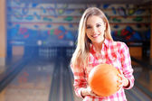 Young woman holding bowling ball in club — Stock Photo