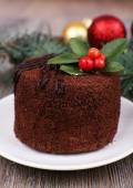 Delicious chocolate cake on saucer with holly and berry on Christmas decoration and wooden background — Stock Photo