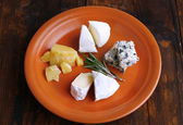 Slices of different sort of cheese on plate on wooden table background — Stockfoto