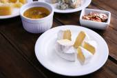 Various types of cheese on plates with  snacks on saucers on wooden table background — Stock Photo