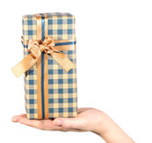 Female hand holding present box with ribbon on light background — Stock Photo