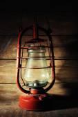 Kerosene lamp on wooden planks background — Stock fotografie