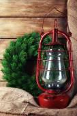 Lâmpada de querosene com coroa de flores sobre fundo de pranchas de madeira — Fotografia Stock