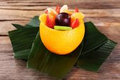 Fruit dessert in orange peel on green leaf on table — Foto de Stock