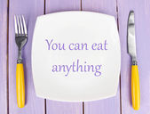 "Plate with text ""You can eat anything"", fork and knife on wooden background — Stock Photo"