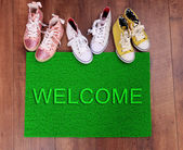 Green carpet on floor and converse close-up — Stock Photo