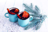 Mugs of mulled wine with piece of orange and spice on color wooden table background — Stock Photo