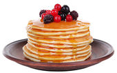 Stack of delicious pancakes with berries and honey isolated on white — Stock Photo