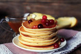 Stack of delicious pancakes with slices of apple and berries on plate and napkin on wooden background — Stock Photo