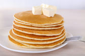 Stack of delicious pancakes with butter on table and light background — Stock Photo