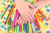 Multicolor female manicure with stationery on bright background — Stock Photo