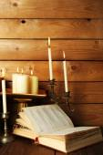 Retro candlesticks with candles and books, on wooden background — Stock Photo