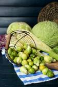 Still life with assortment cabbages on cutting board on color wooden background — Stock Photo