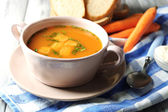 Carrot soup, cream and spoon, on  color wooden background — Stock Photo