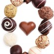 Oval from sweet truffles on white background with chocolate heart in the middle — Stock Photo #62315251