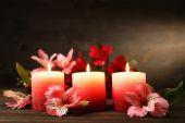 Belle candele con fiori sul tavolo di legno, su sfondo scuro — Foto Stock