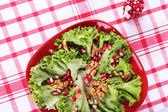 Fresh salad with greens, garnet and spices on plate on table close-up — Stock Photo