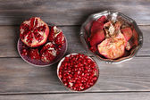 Beautiful composition with juicy  pomegranate seeds, on old wooden table — Zdjęcie stockowe