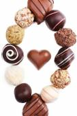 Oval from sweet truffles on white background with chocolate heart in the middle — Stock Photo